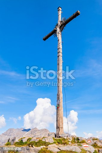 istock Wooden cross on a mountain footpath (Livigno, Italy) 1329464636