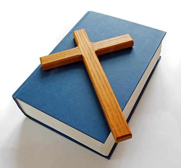Wooden cross on bible stock photo