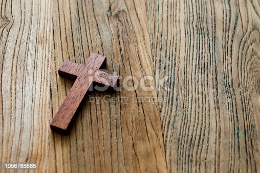Wooden cross on desk background.