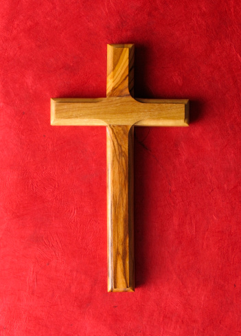 A wooden cross on a red grunge paper background.