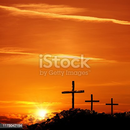 close up group of wooden cross on rocky hill over sunset sky