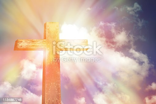 wooden cross shape on rocky hill at sunset with blue sky and clouds background, religion symbol concept