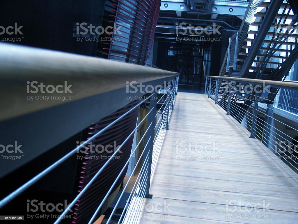 wooden crosswalk with banisters inside a building. royalty-free stock photo