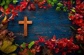 wooden crucifix cross in autumn leaves border and blue wood table board background copy space