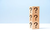 Wooden cube block shape with sign question mark symbol on blue background