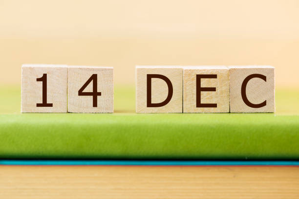 Wooden cube shape calendar for DEC 14 on green book, table. stock photo