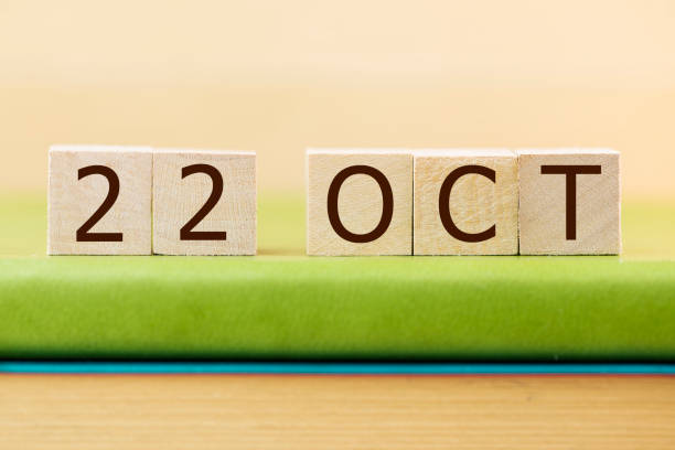 Wooden cube shape calendar for OCT 22 on green book, table. stock photo