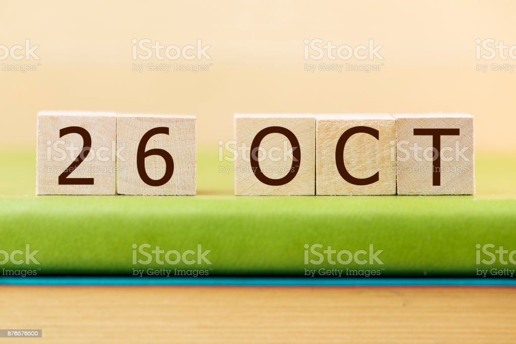 Wooden cube shape calendar for OCT 26 on green book, table. stock photo