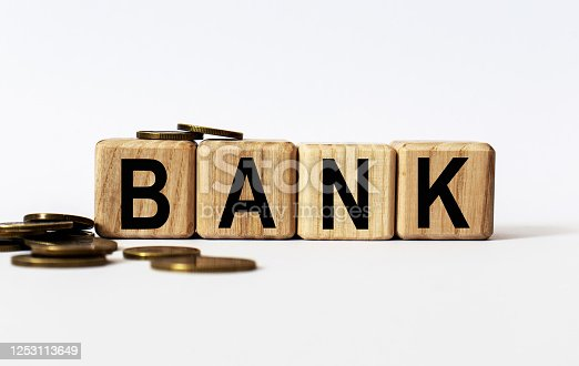 947260978 istock photo wooden cubes and BANK, coins, the concept of taxation, increase taxes and fees 1253113649