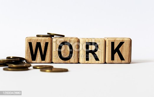 947260978 istock photo wooden cubes and WORK, coins, the concept of taxation, increase taxes and fees 1253342880