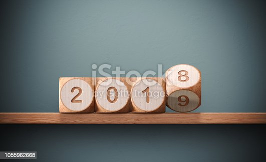 Wooden cubes are rotating from 2017 to 2018 in front of a grey wall. Numbers are engraved on toy blocks. New year and change concept.  Horizontal composition with copy space.
