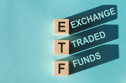 Tile letter on red rack in word ETF (abbreviation of Exchange Traded Fund) on wood background