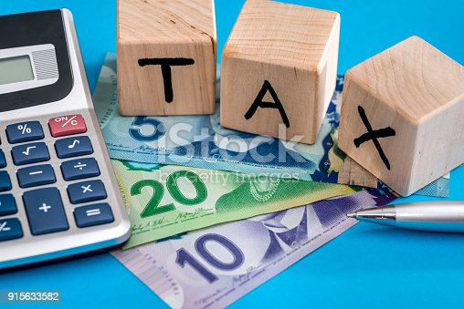 istock Wooden cubes tax with canadian dollar 915633582