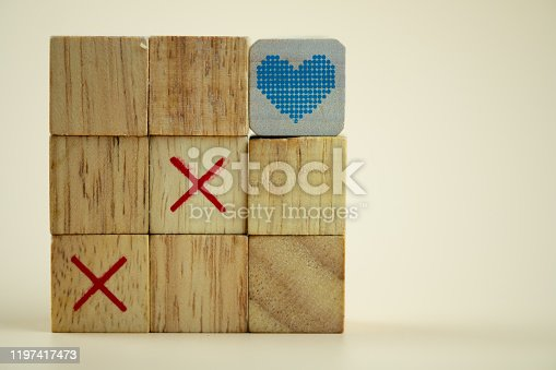 Wooden cubes tic tac toe board game with cubes heart on top. Concept of love