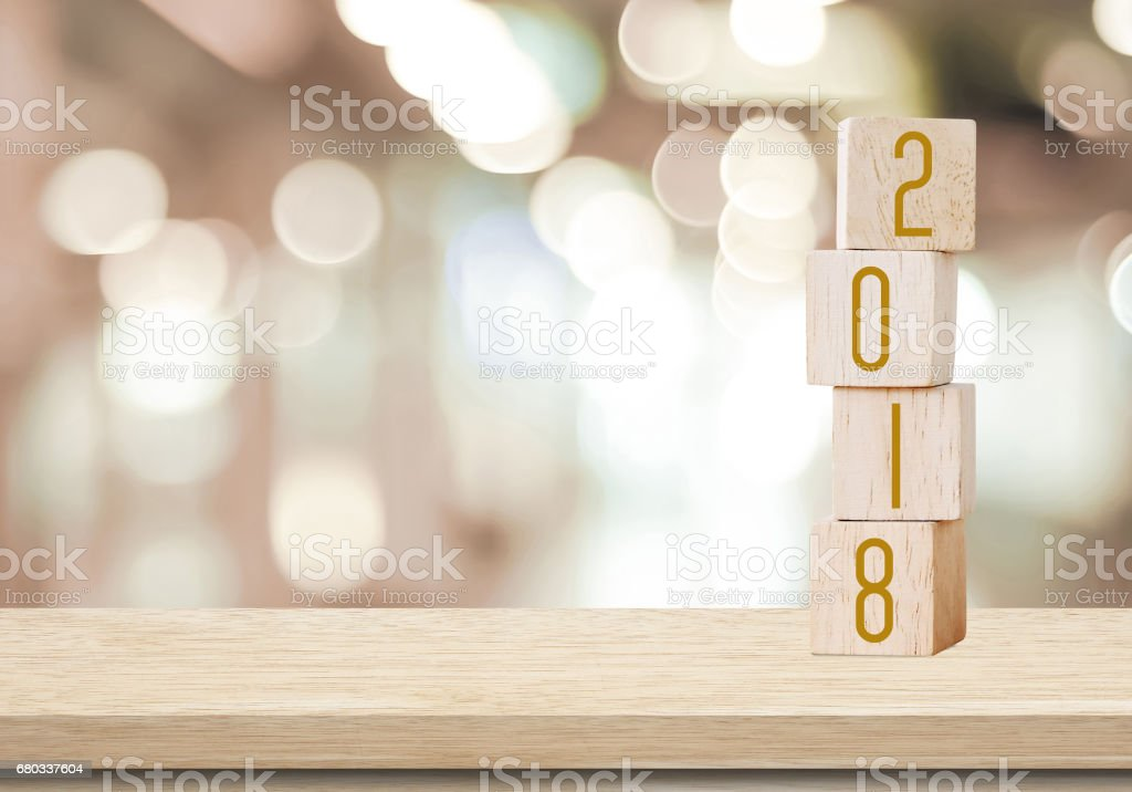 Wooden cubes with 2018 on perspective wood over blur bokeh background with copy space for text, new year template stock photo