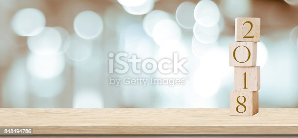 istock Wooden cubes with 2018 on perspective wood over blur bokeh background, banner with copy space for text, new year template 848494786