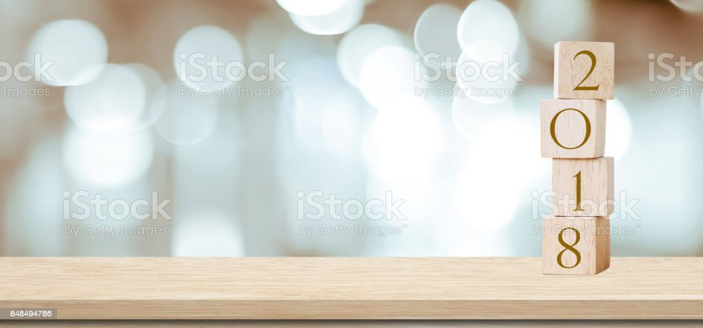 Wooden cubes with 2018 on perspective wood over blur bokeh background, banner with copy space for text, new year template stock photo