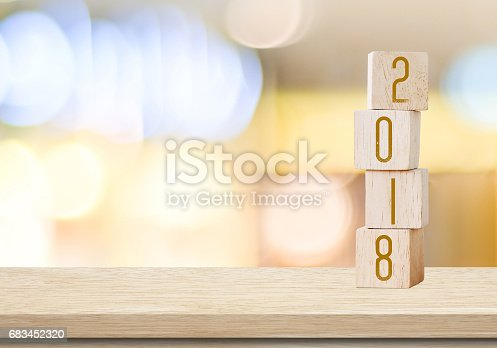 istock Wooden cubes with 2018 on table over blur bokeh background with copy space for text, new year and christmas card background,template 683452320