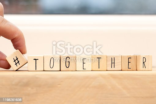 1016771914 istock photo Wooden cubes with a hashtag and the word Together, social media concept space for text 1198261638