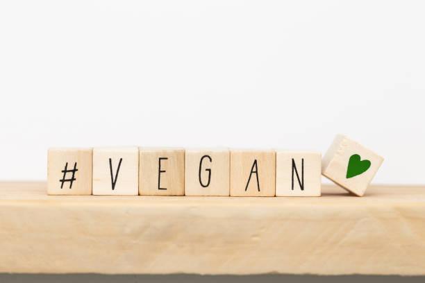 cubos de madera con un hashtag y la palabra vegana, fondo conceptual de las redes sociales - vegana fotografías e imágenes de stock