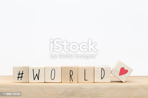 Wooden cubes with a hashtag and the word World, social media concept near white background close-up