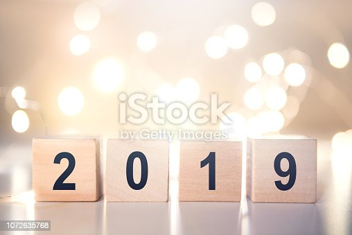 1009979852 istock photo Wooden cubes with Happy new year 2019 with light bokeh background with copy space for text. 1072635768