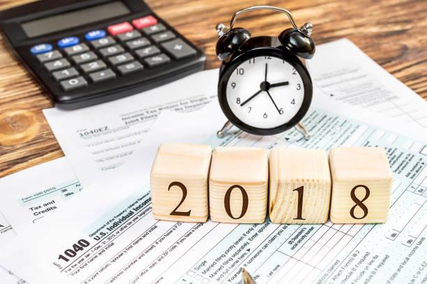 """houten blokjes met getallen """"2018"""" met belasting vormen en rekenmachine op de tafel. bedrijfsconcept. belasting betalen in 2018 jaar. - 2018 stockfoto's en -beelden"""