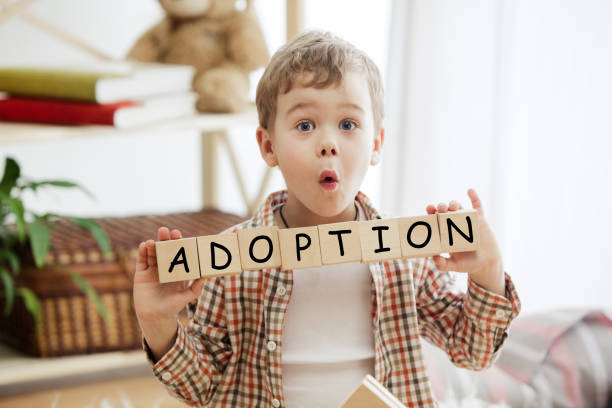 Wooden cubes with word adobtion in hands of little boy Wooden cubes with word adobtion in hands of little boy at home. Conceptual image about child rights, education, childhood and social problems. prettige verrassingen stock pictures, royalty-free photos & images