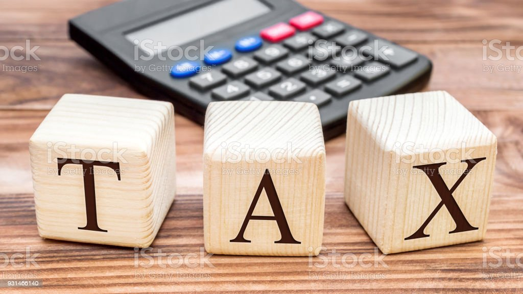 Wooden cubes with word TAX and calculator on the table. Business concept. Top view. stock photo