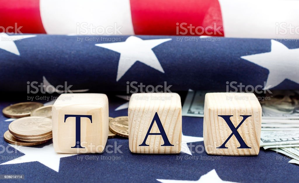 Wooden cubes with word ' Tax ' and money on the american flag. Business concept. stock photo