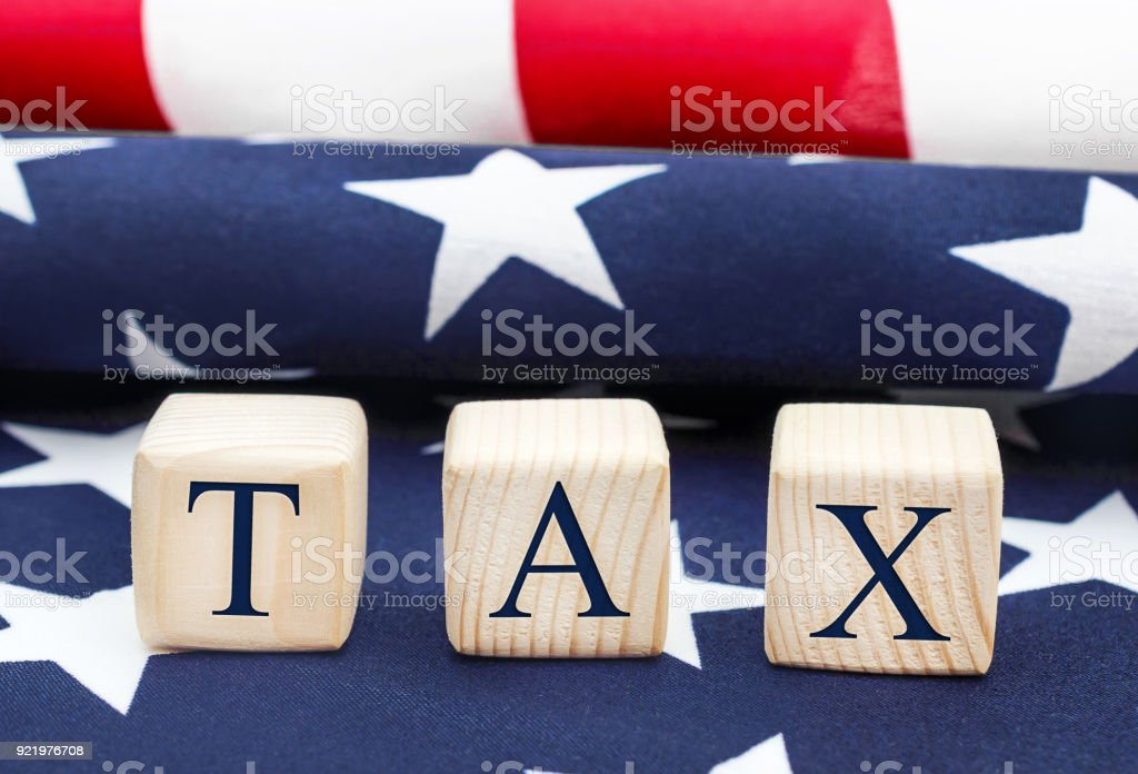 Wooden cubes with word ' Tax ' on the american flag. Business concept. stock photo
