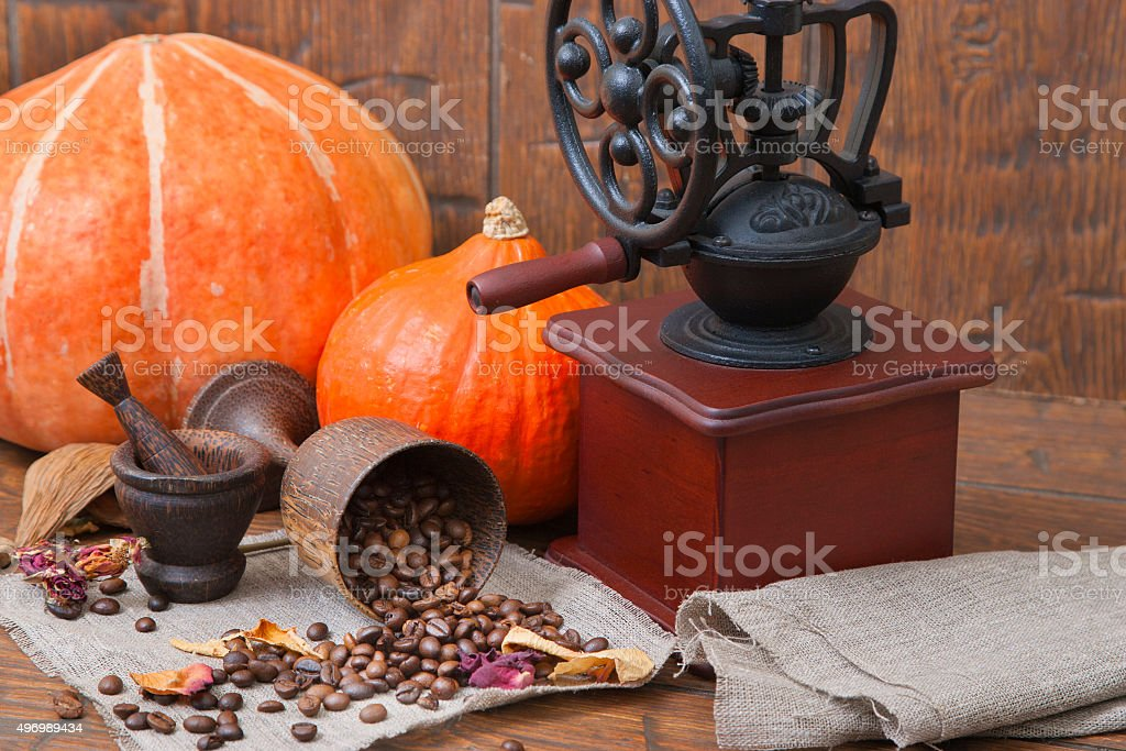 Wooden cup with coffee and grinder on the autumn background stock photo