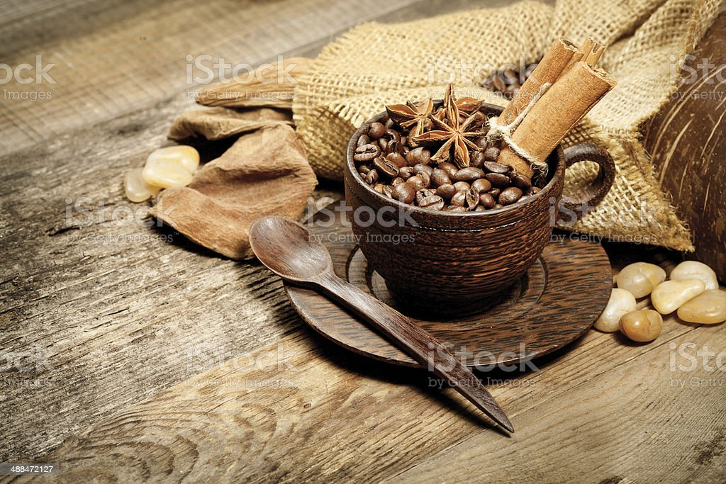 Wooden cup with coffee-beans on wooden table royalty-free stock photo