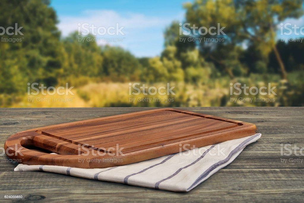 Wooden Cutting Board On The Picnic Table And Summer Lan stock photo