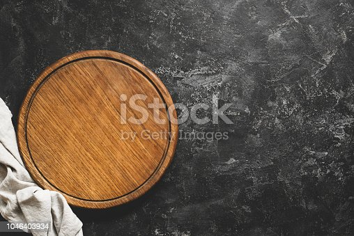 istock Wooden cutting board or pizza board on black concrete background 1046403934