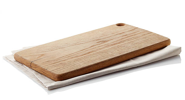 Wooden cutting board Brown wooden cutting board on cotton napkin isolated on white background. Clipping path cutting board stock pictures, royalty-free photos & images