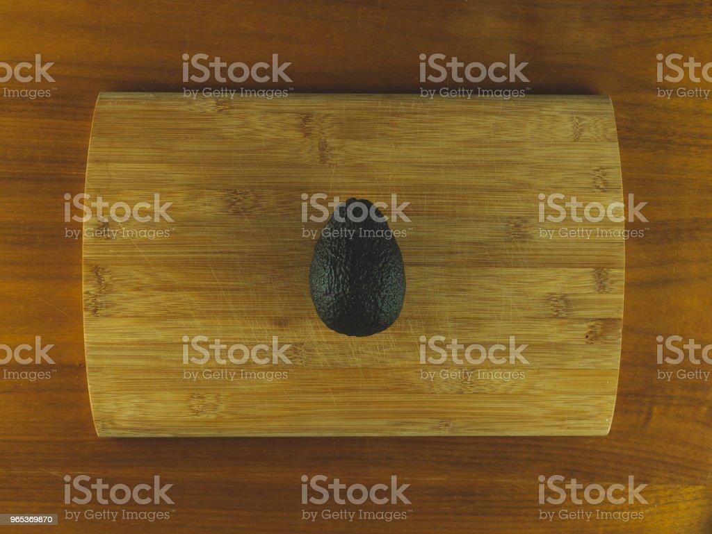 Wooden cutting board with an avocado zbiór zdjęć royalty-free