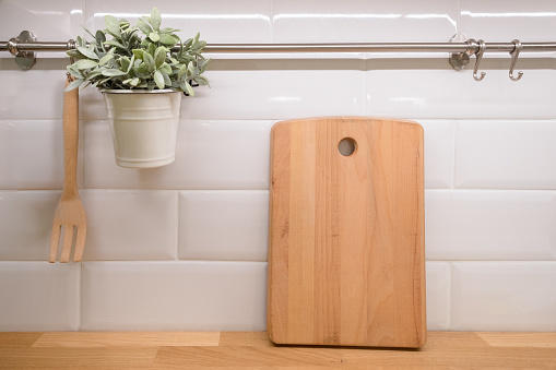 Wooden cutting board with Kitchen utensils on wooden Countertop. Kitchen interior background