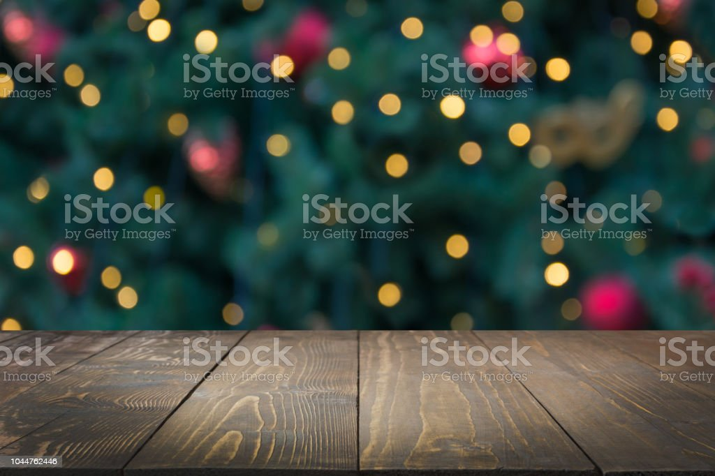 Wooden dark tabletop and blurred christmas tree bokeh. Xmas background for display your products. - Foto stock royalty-free di Albero