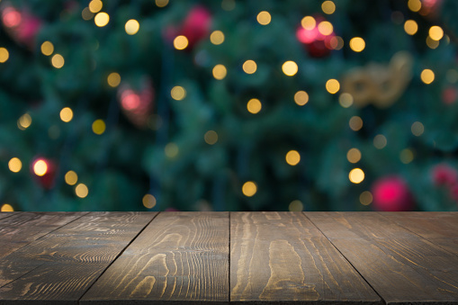 Wooden dark tabletop and blurred christmas tree bokeh. Xmas background for display your products.