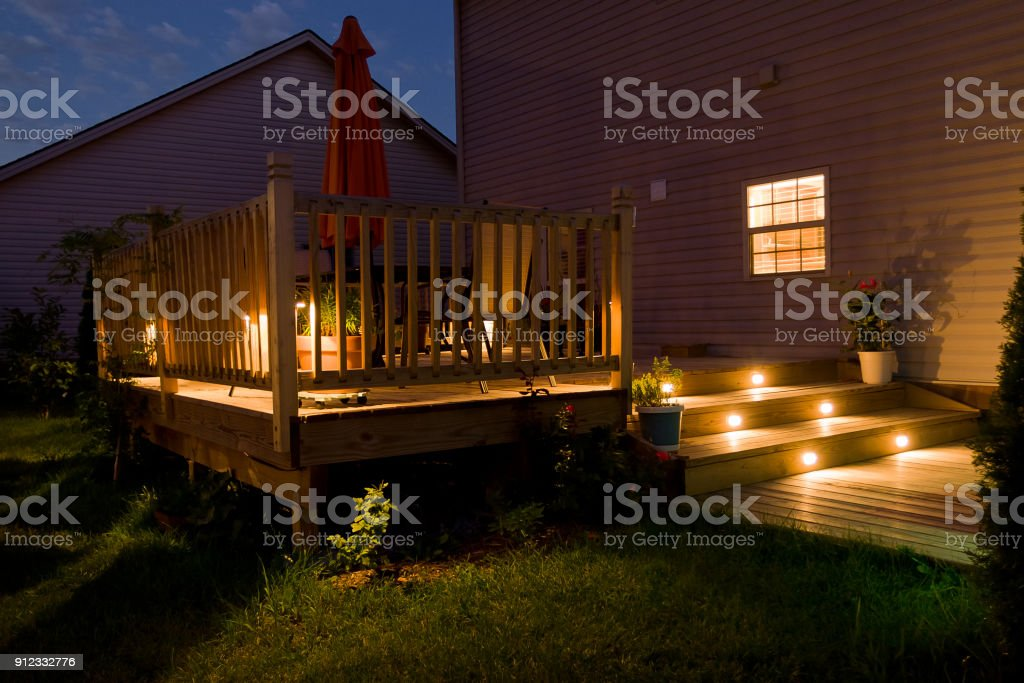 Wooden deck and patio of family home at night. stock photo