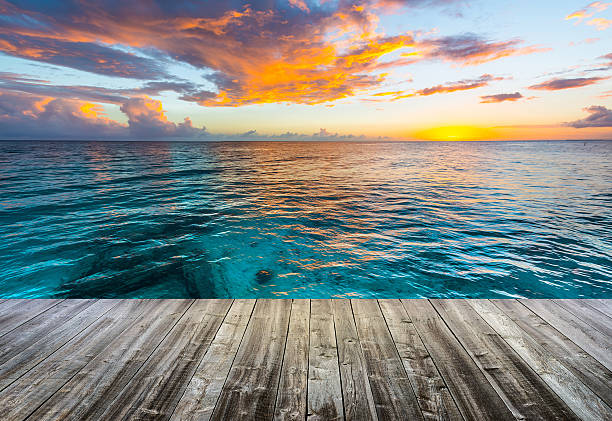 wooden deck at caribbean sea at sunset stock photo