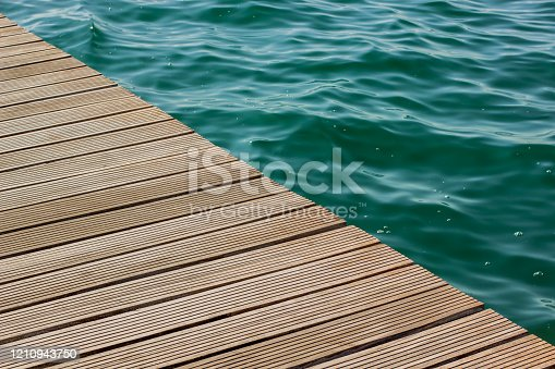 677933036 istock photo wooden deck floor background texture diagonal line and vivid blue and green water with small waves on a surface in big swimming pool, copy space pattern 1210943750