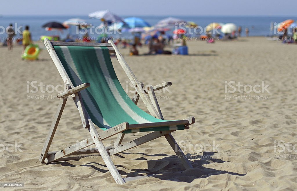 wooden deck on sunny beach with many umbrellas stock photo