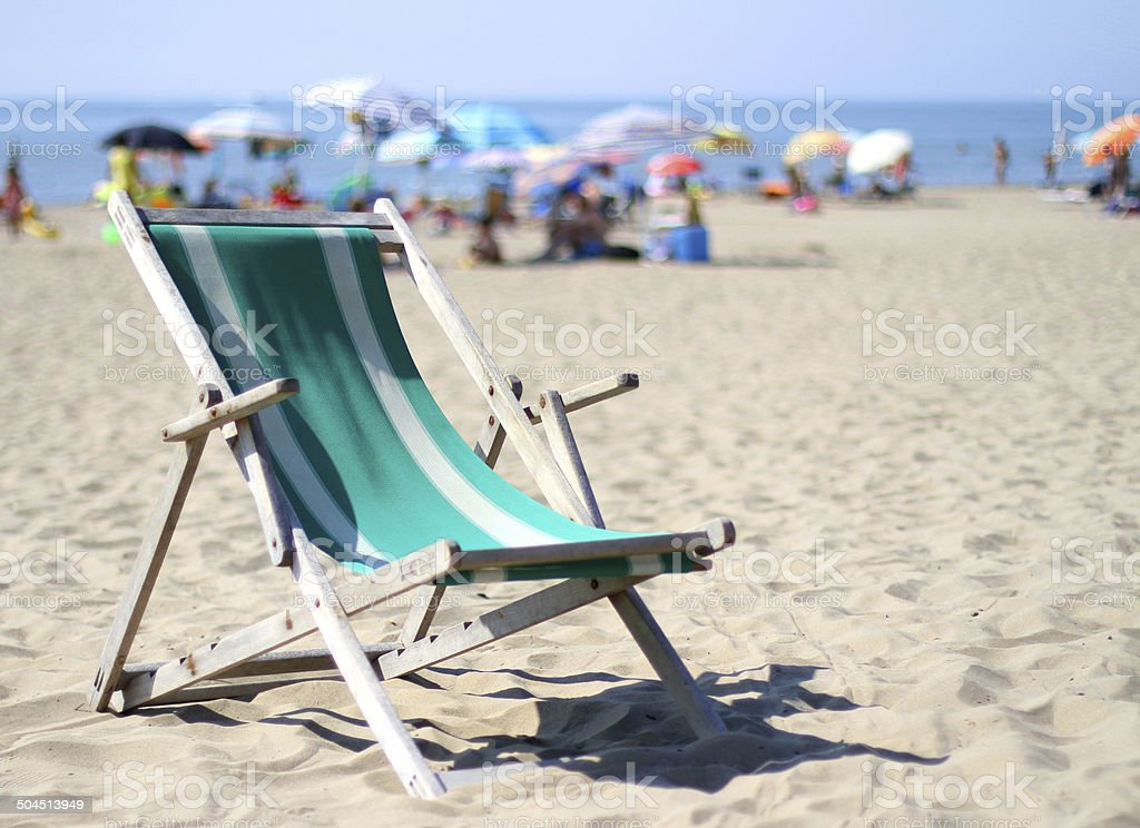 wooden deck on sunny beach with umbrellas in summer stock photo