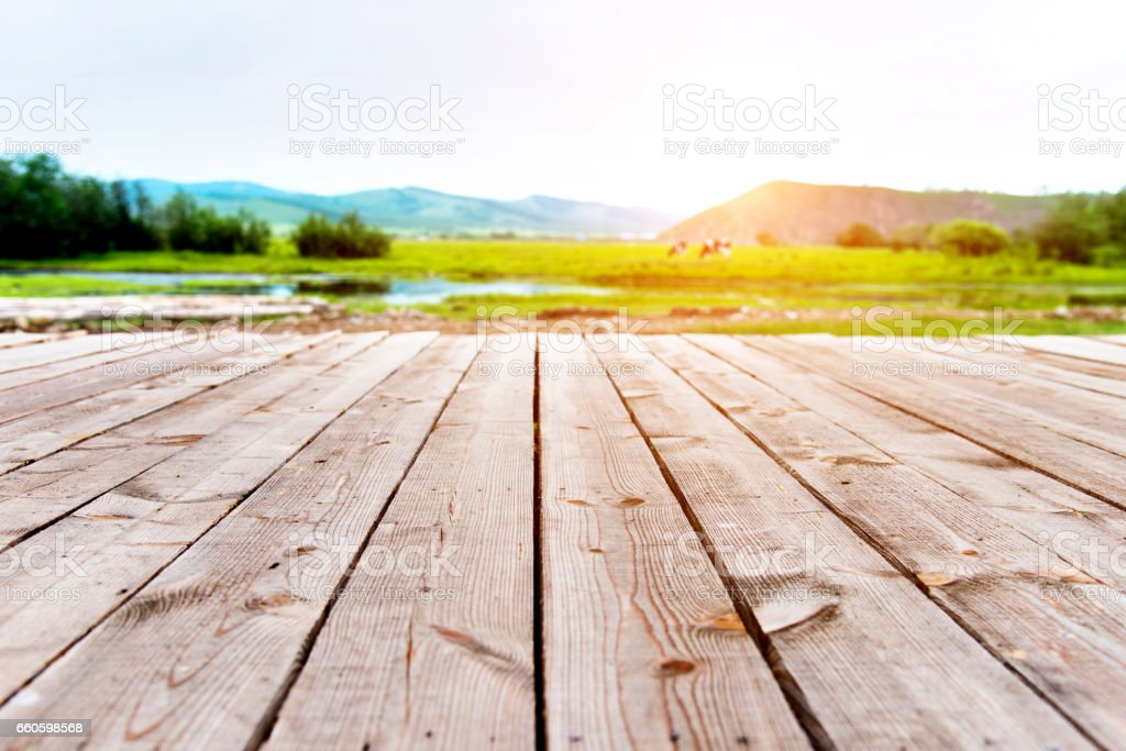 Wooden deck with green nature on the background stock photo
