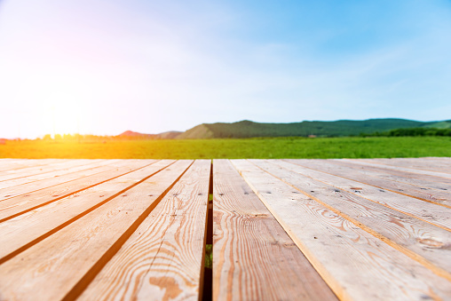 Wooden deck with green nature on the background