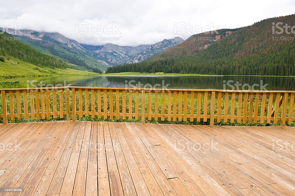 Wooden Deck with Summer Mountain View and Serene Lake royalty-free stock photo