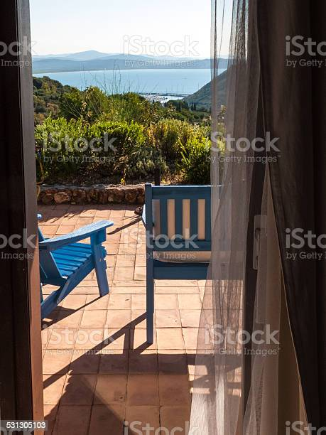 Photo of wooden deckchairs on the patio in front of the sea