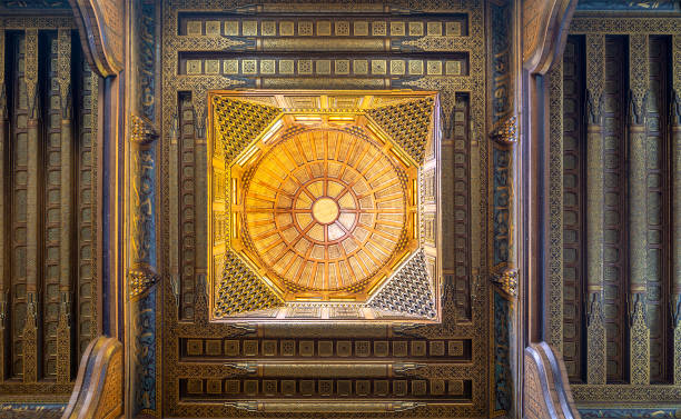 Wooden decorated dome mediating ornate ceiling with floral pattern decorations at al Ghuri Mausoleum, Cairo, Egypt stock photo